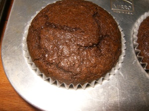 photo of a medium-brown chocolate cupcake with a baked and domed top